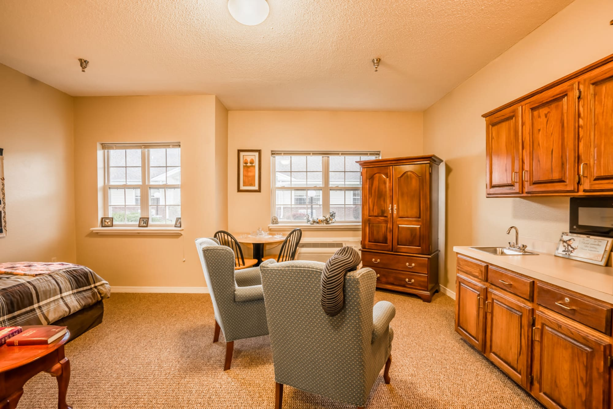 Brightly lit inside of senior living apartment complete with armchair seating and wood cabinets at Saunders House in Wahoo, Nebraska