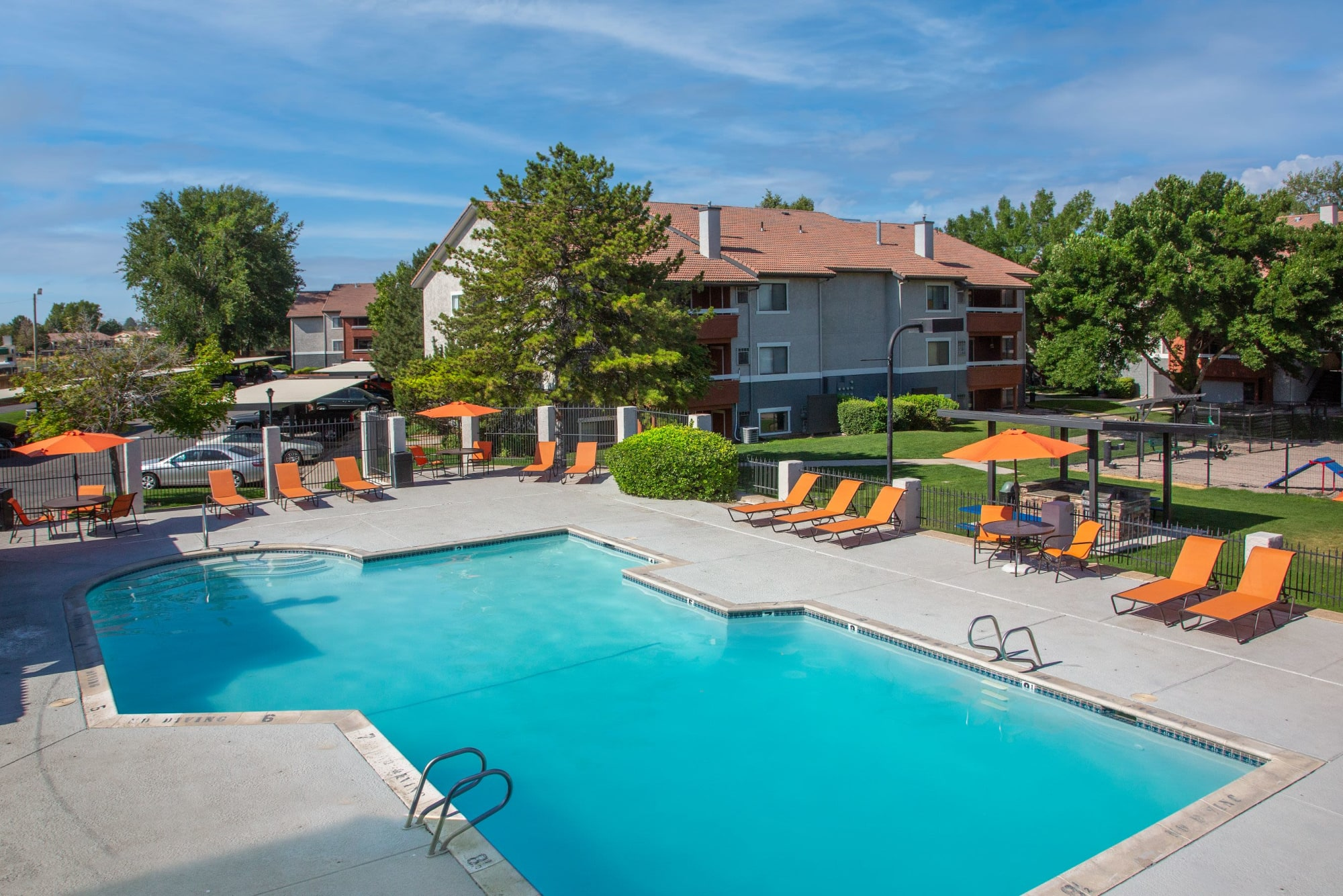 Sparkling community swimming pool with lounge chairs at Shadowbrook Apartments in West Valley City, Utah