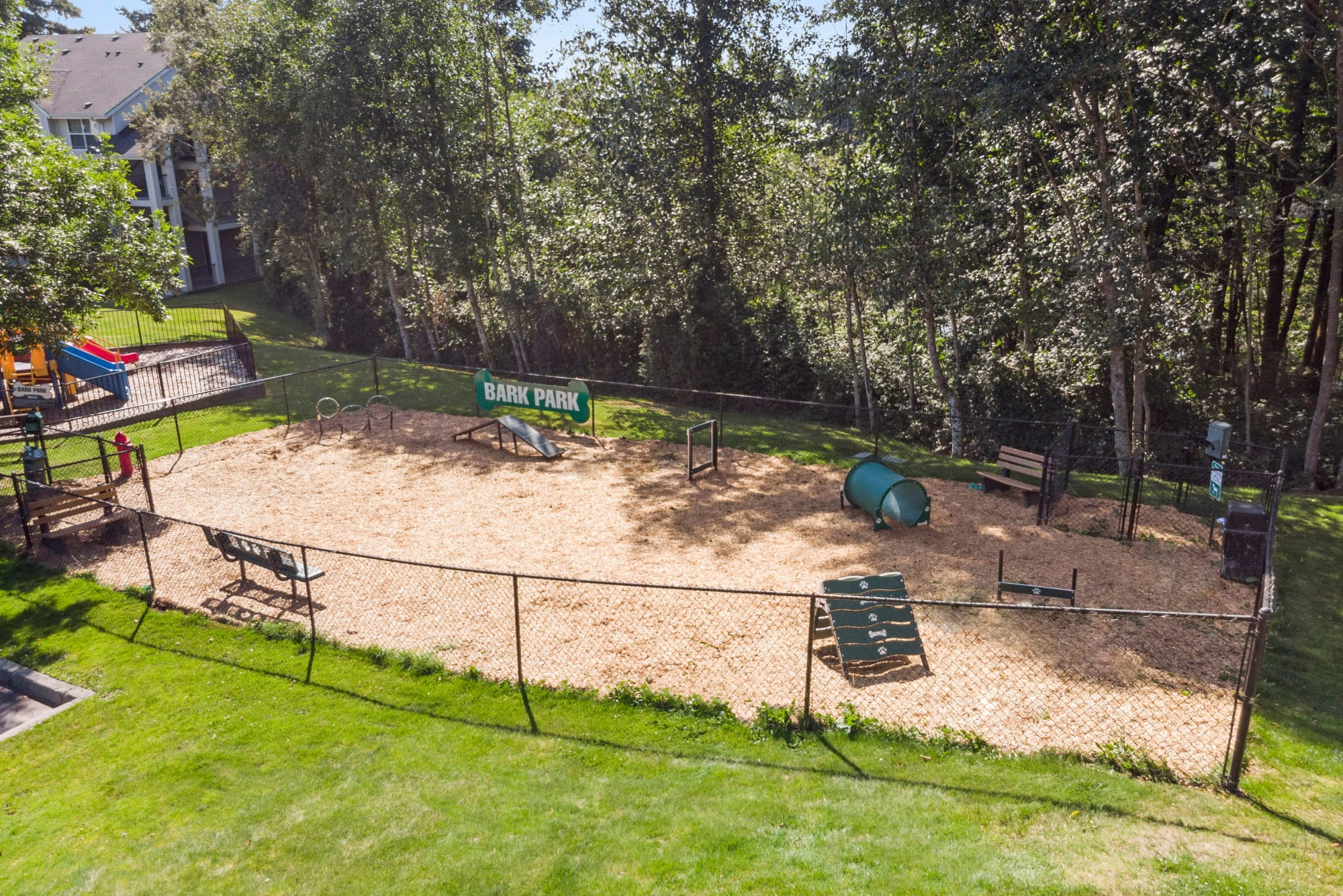 Dog park with lush landscaping and toys and obstacles at HighGrove Apartments in Everett, Washington