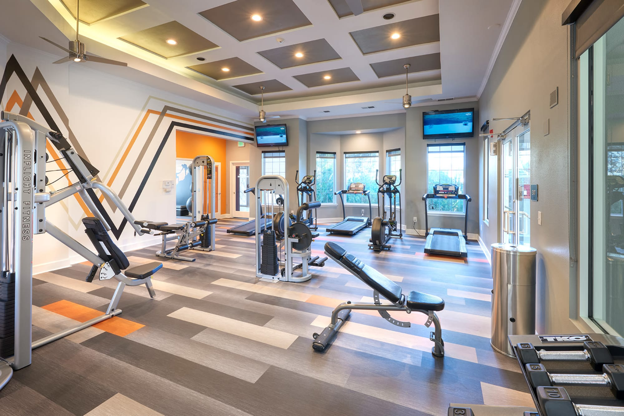 Fitness center with individual workout stations at Legend Oaks Apartments in Aurora, Colorado
