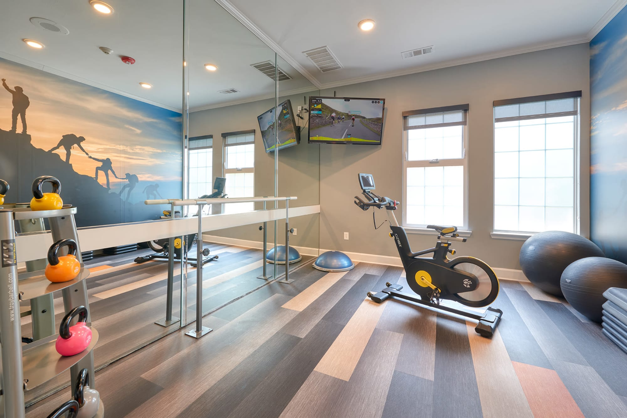 Fitness room with large mirror at Legend Oaks Apartments in Aurora, Colorado