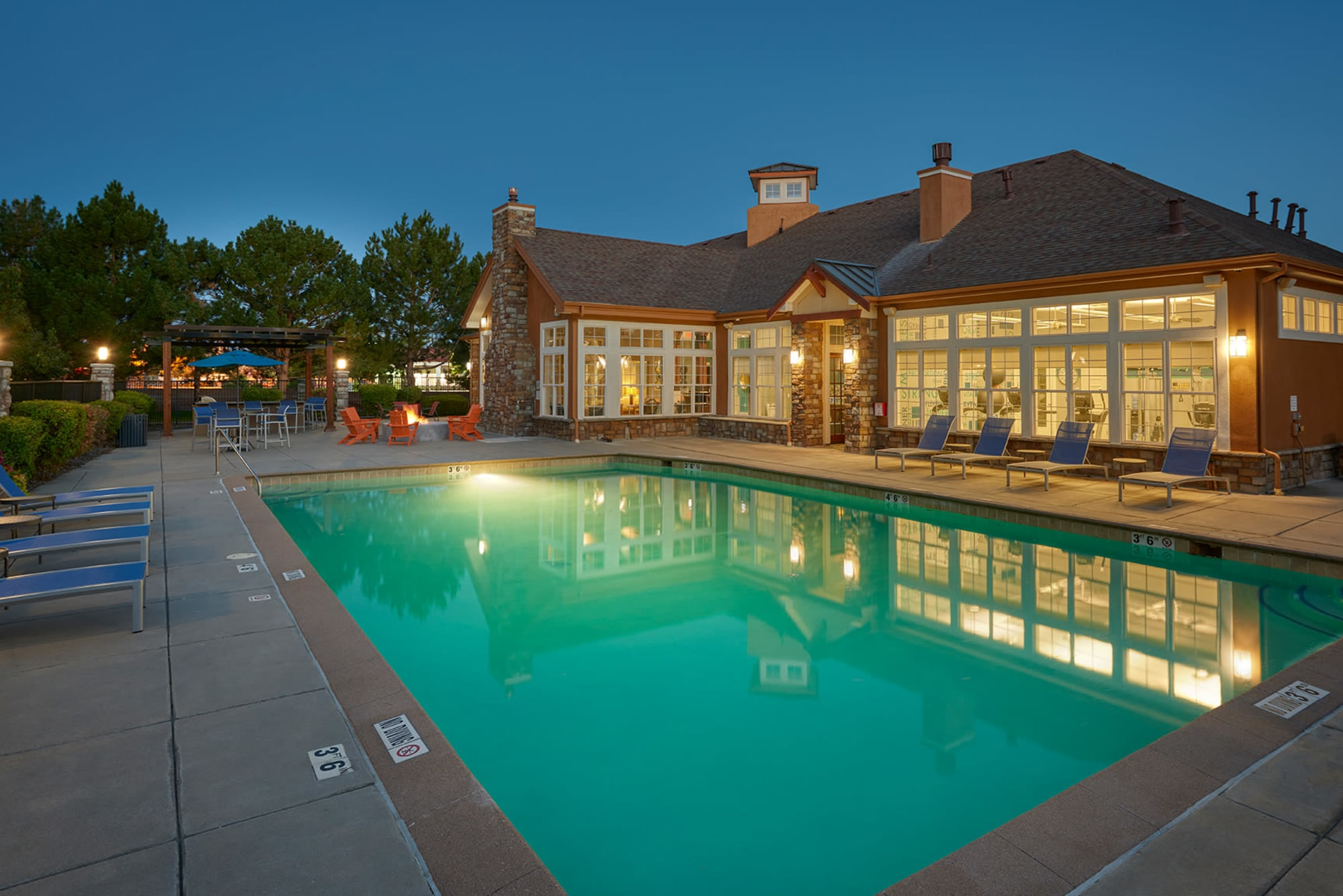 Pool shot with clubhouse and firepit  at Crestone Apartments in Aurora, Colorado