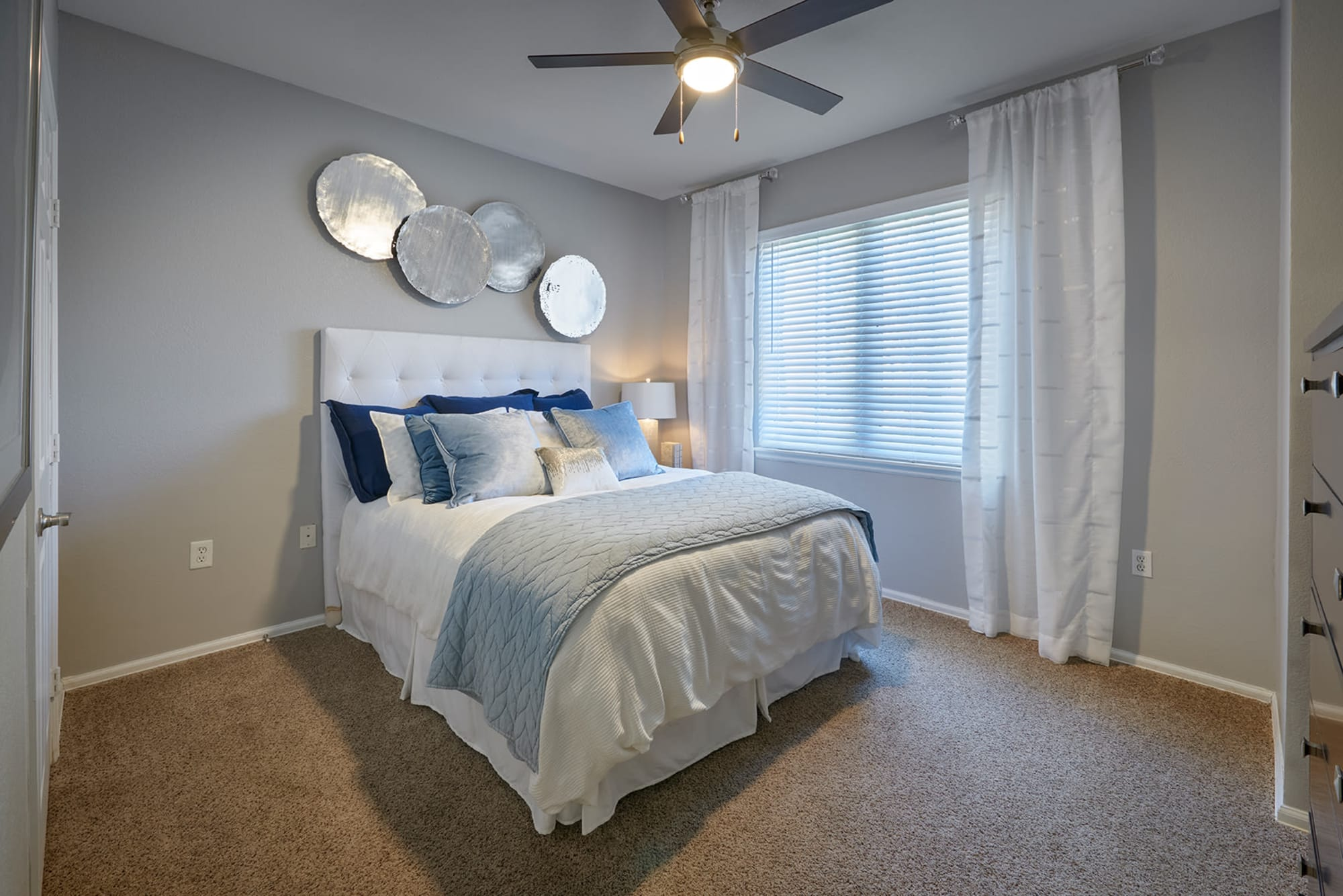 A furnished apartment bedroom at Crestone Apartments in Aurora, Colorado