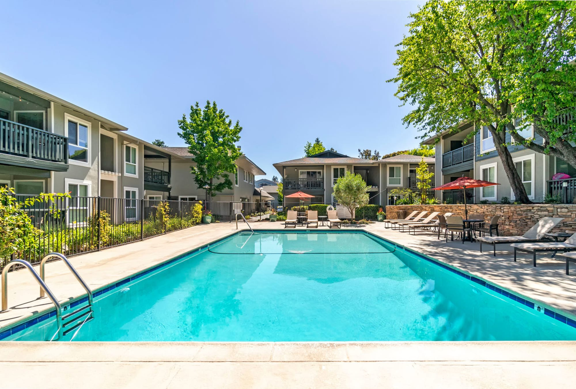 Lounge chairs near the pool at Pleasanton Glen Apartment Homes in Pleasanton, California