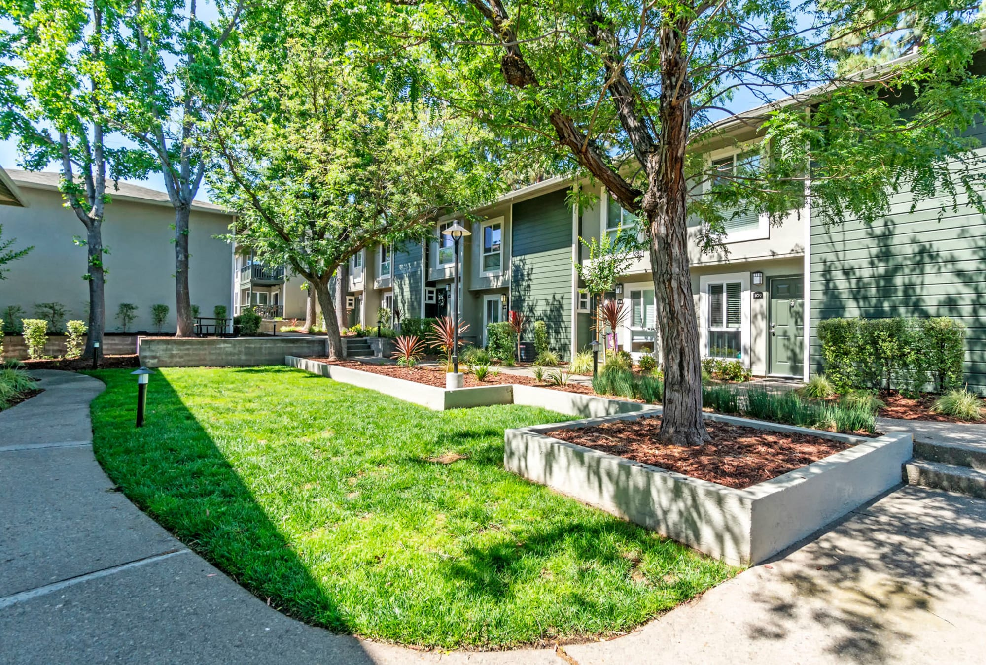 Mature trees and professionally maintained landscaping at an exterior courtyard at Pleasanton Glen Apartment Homes in Pleasanton, California