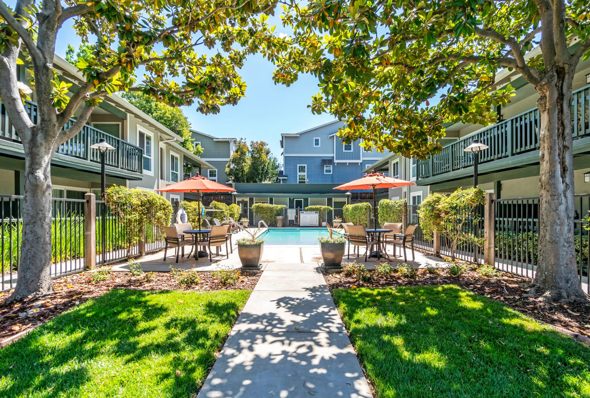 Shaded green grass along a pathway leading to the swimming pool area at Pleasanton Glen Apartment Homes in Pleasanton, California