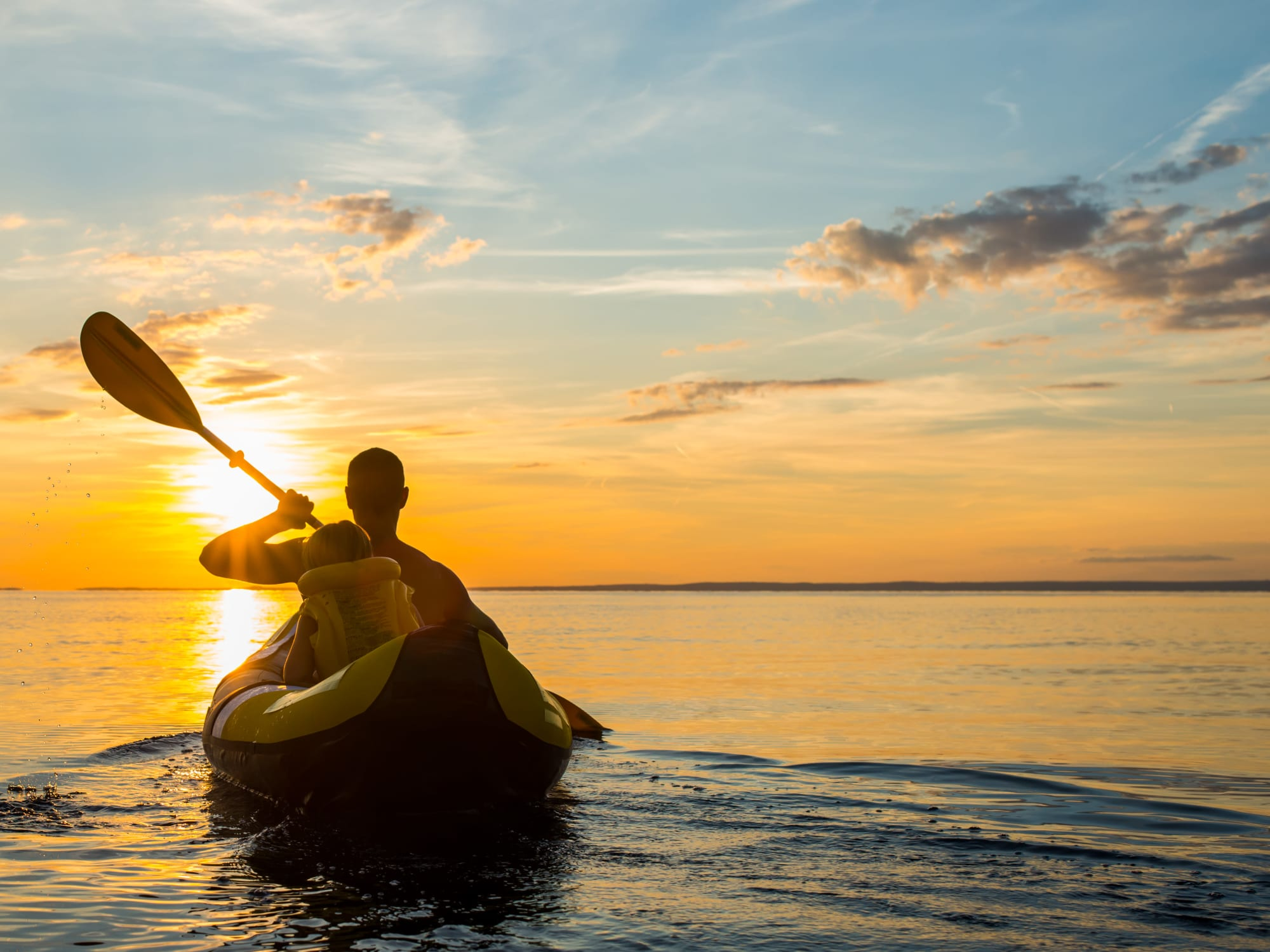 Resident father and son kayaking at sunset near Waters Edge at Marina Harbor in Marina Del Rey, California