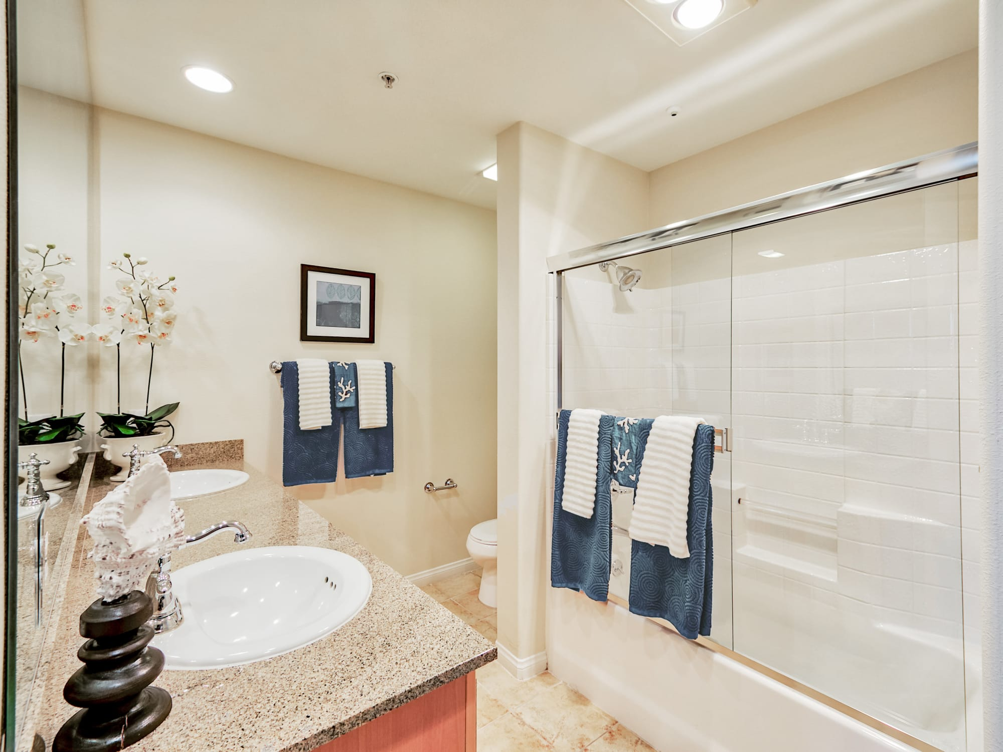 Spacious bathroom with granite countertop, double sink and shower at The Villa at Marina Harbor in Marina del Rey, California