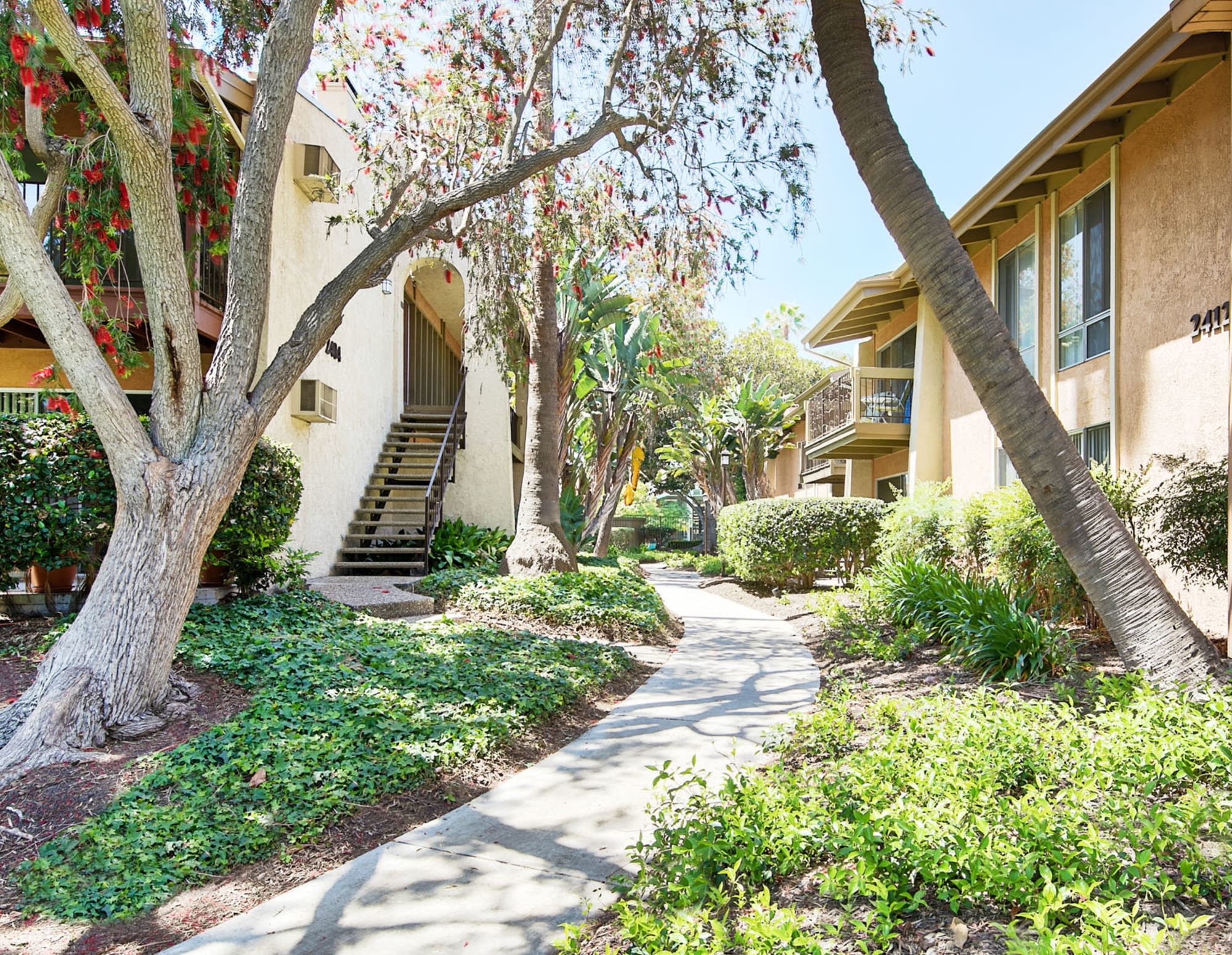 Lush and well-manicured landscaping along a community pathway at Mediterranean Village Apartments in Costa Mesa, California