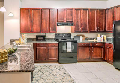 Cherry cabinets and black appliances in model apartment kitchen at Villas at Bunker Hill