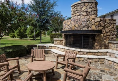 Outdoor patio seating next to a fireplace at Ranch ThreeOFive in Arlington, Texas