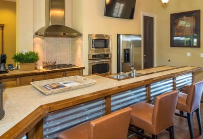 Clubhouse with a full kitchen and bar seating at Ranch ThreeOFive in Arlington, Texas