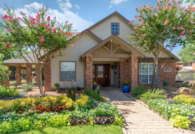 Exterior with a beautifully manicured landscape at The Logan in Bedford, Texas