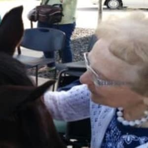 Resident Mary petting a horse at her Dare to Dream event at Milestone Senior Living in Stoughton, Wisconsin