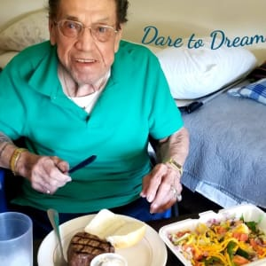 Resident Louie enjoying a steak dinner at his Dare to Dream event at Landings of Blaine in Blaine, Minnesota
