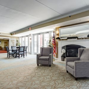 Interior lounge area with a fireplace and grey seating at Hanover Place in Tinley Park, Illinois