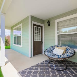 Back porch of a residence with a comfy papasan chair at Sunstone Village in Denton, Texas