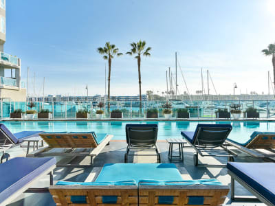 Resort-style swimming pool with underwater lap lanes and lounge chairs overlooking the marina at Esprit Marina del Rey in Marina del Rey, California
