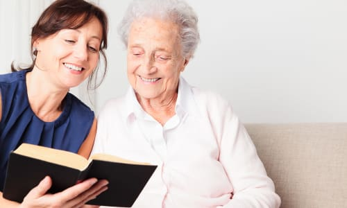 A caretaker at Battle Creek Memory Care reading a book with a resident in Salem, Oregon