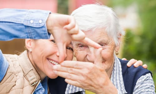 A caretaker at Battle Creek Memory Care posing with a resident in Salem, Oregon