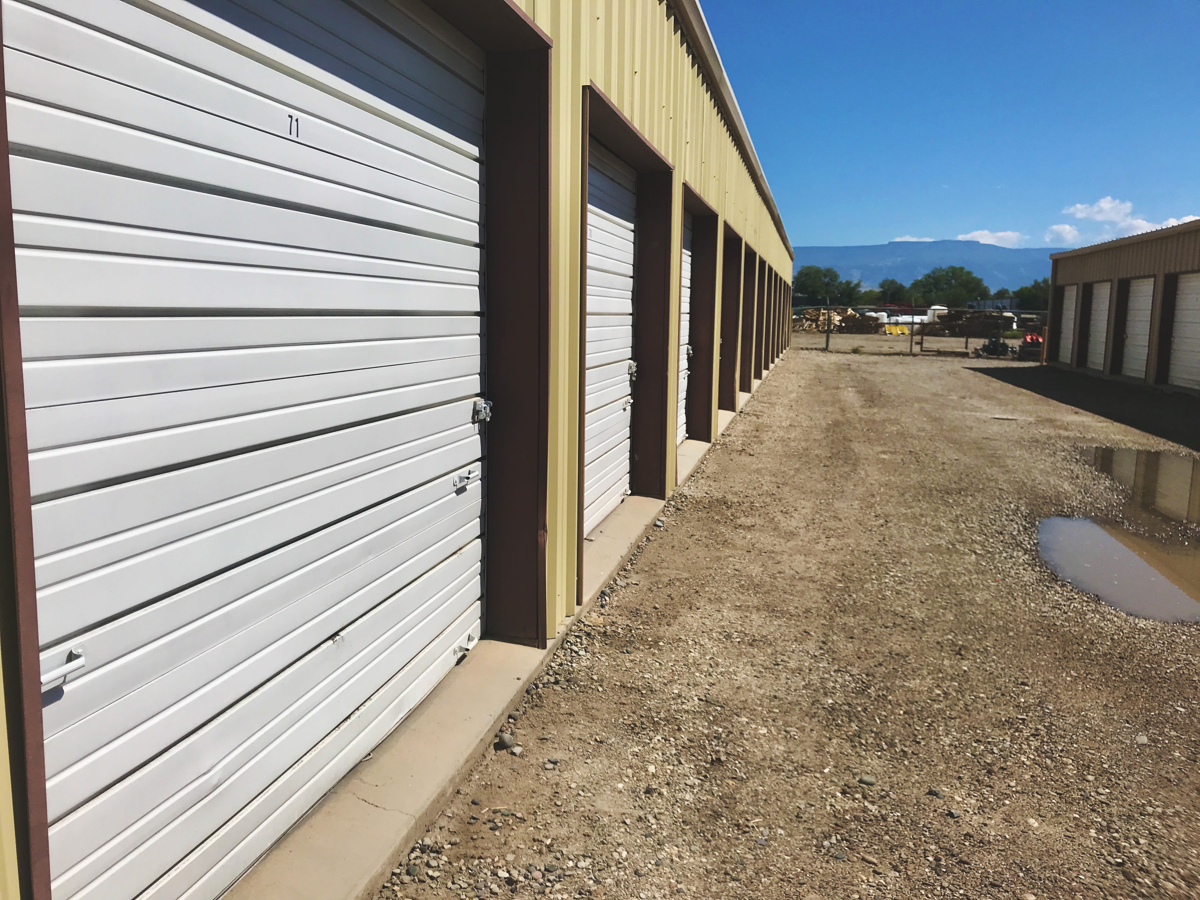 A row of outdoor units with green doors at 603 Storage - Dudley in Raymond, New Hampshire