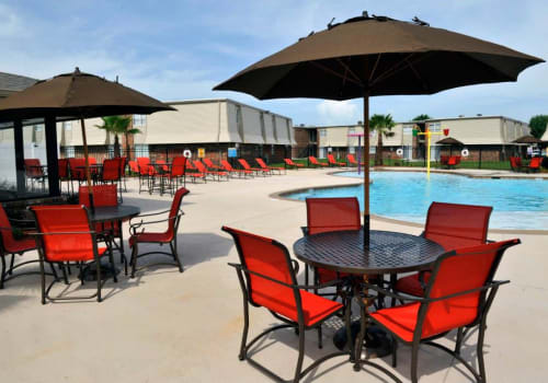Swimming pool with covered seating area at Emerald Pointe Apartment Homes in Harvey, Louisiana