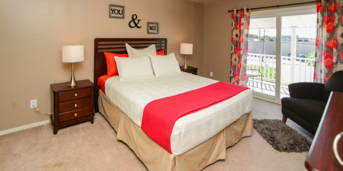 Red and white colors featured prominently in model bedroom at Greentree Village Townhomes in Lebanon, PA