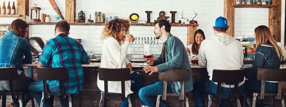 A couple discusses something over drinks at a local bar near Hawthorne Hill Apartments in Thornton, Colorado