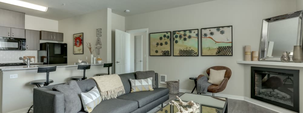 Living Room and Kitchen with Fireplace in an apartment at pet-friendly Terrene at the Grove in Wilsonville, Oregon