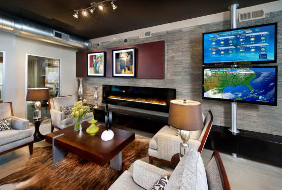 Comfortable seating in front of the fireplace in the resident clubhouse at Perimeter Lofts in Charlotte, North Carolina