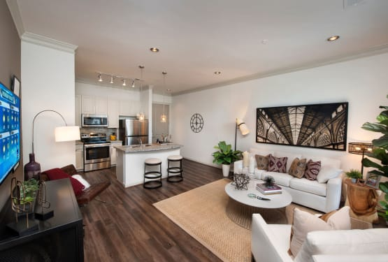 Hardwood-style flooring and modern furnishings in the living areas of a model apartment at The Heights at Sugarloaf in Duluth, Georgia