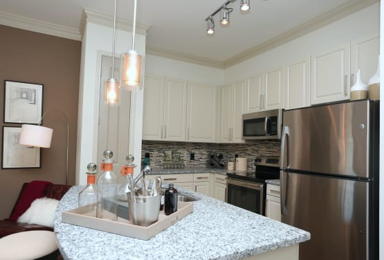Granite countertops and stainless-steel appliances in a model apartment's kitchen at The Heights at Sugarloaf in Duluth, Georgia