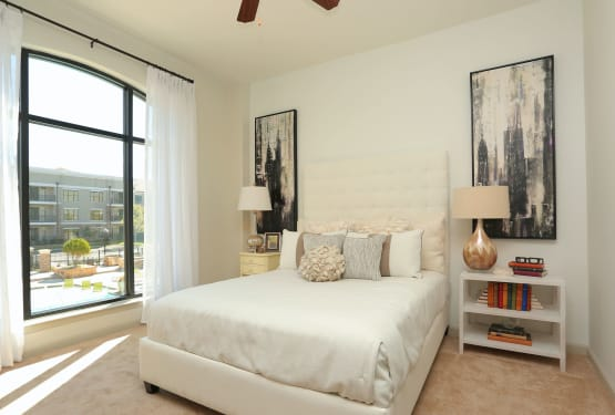 Plush carpeting and floor-to-ceiling windows in a model home's primary bedroom at The Heights at Sugarloaf in Duluth, Georgia