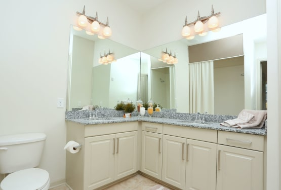 Spacious primary bathroom with large vanity mirrors in a model home at The Heights at Sugarloaf in Duluth, Georgia