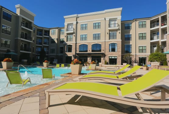 Resort-style swimming pool with plenty of chaise lounge chairs at The Heights at Sugarloaf in Duluth, Georgia