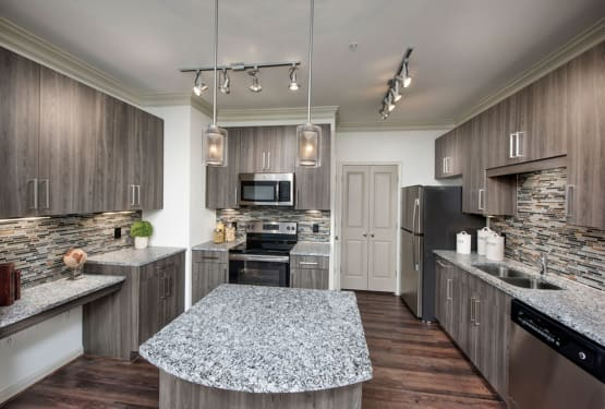 Chef-inspired kitchen with custom lighting over the breakfast bar in a model home at The Heights at Sugarloaf in Duluth, Georgia