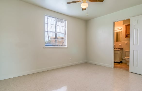 View of master bedroom with ensuite bathroom in apartment home at Bossier East Apartments
