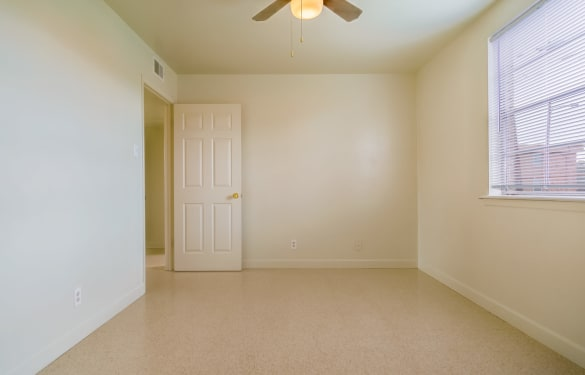 Spacious bedroom view with ceiling fan and natural light at Bossier East Apartments in Bossier City