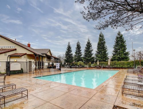 Pool with plenty of lounge chairs at Laguna Creek Apartments in Elk Grove, California