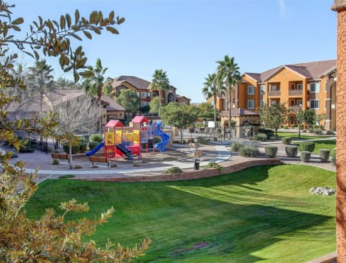 Children's playground surrounded by a grass lawn at Tierra Pointe in Casa Grande, Arizona