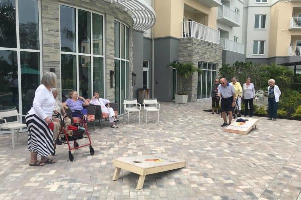 Residents enjoying cornhole at All Seasons Naples in Naples, Florida