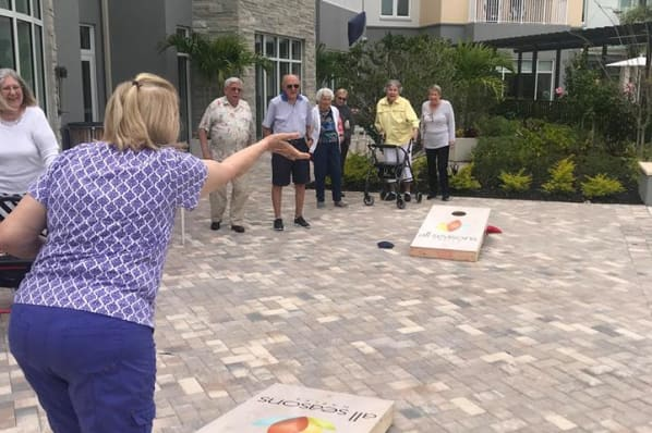 Resident playing cornhole at All Seasons Naples in Naples, Florida