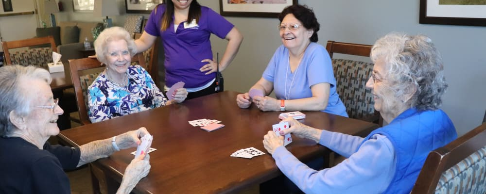 Residents playing cards with caregiver in the background at The Springs at Grand Park in Billings, Montana