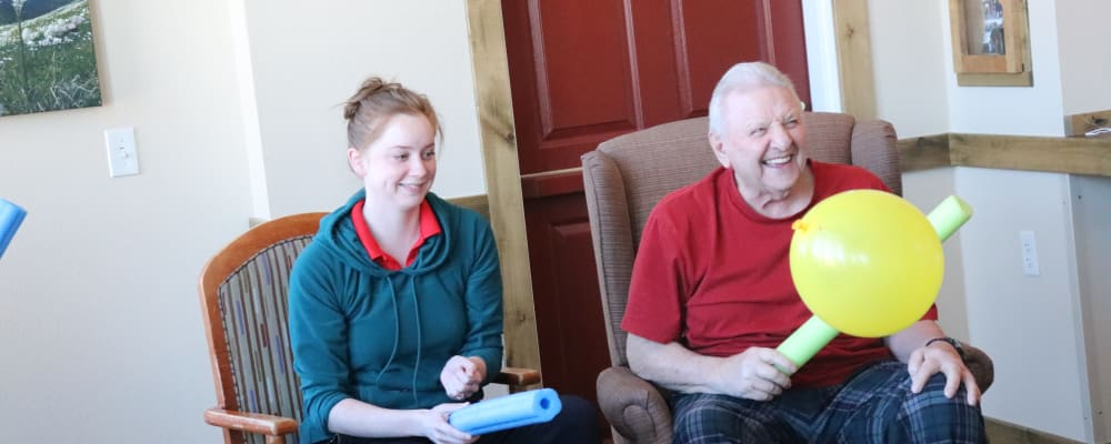 Resident and caregiver playing balloon game at The Springs at Whitefish in Whitefish, Montana