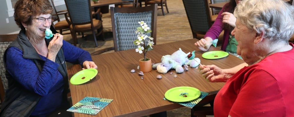 Residents laughing and having a snack with caregiver at The Springs at Sherwood in Sherwood, Oregon