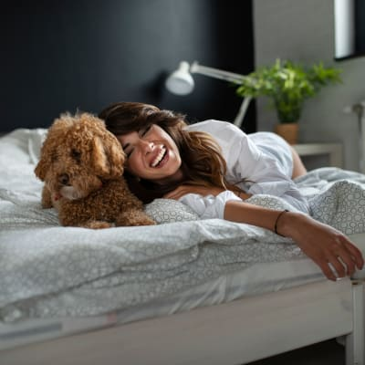 Happy dog and resident laying in bed at Two Twelve Clayton in Clayton, Missouri