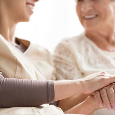 Resident smiling and holding hands with on-site nurse at Westminster Memory Care in Aiken, South Carolina