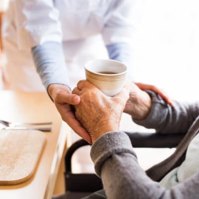 Staff handing a resident a cup of coffee at Westminster Memory Care in Aiken, South Carolina
