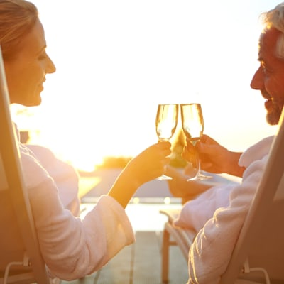 Resident couple toasting to the good life at sunset from their private balcony at The Station at River Crossing in Macon, Georgia