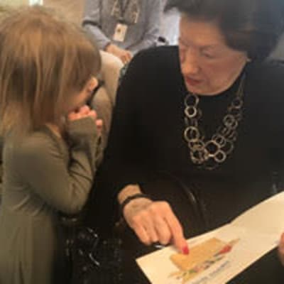 Resident reading with a young child at an intergenerational activity at Deephaven Woods in Deephaven, Minnesota